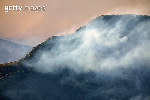 Smoke clouds from forest fires drifts in valley and clings to mountain ridge at dusk, Blue Mountains, Australia - gettyimageskorea