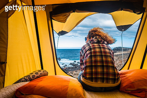 Rear View Of Mature Woman Sitting In Tent At Beach - gettyimageskorea