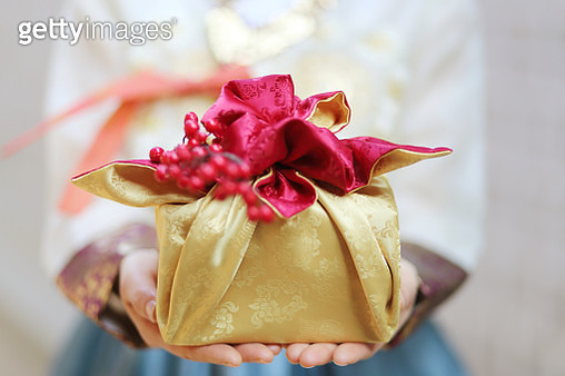Woman in Korean traditional clothes with traditional package - gettyimageskorea