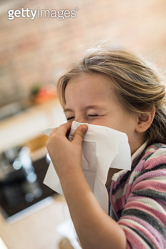 Small girl blowing her nose into a napkin. - gettyimageskorea