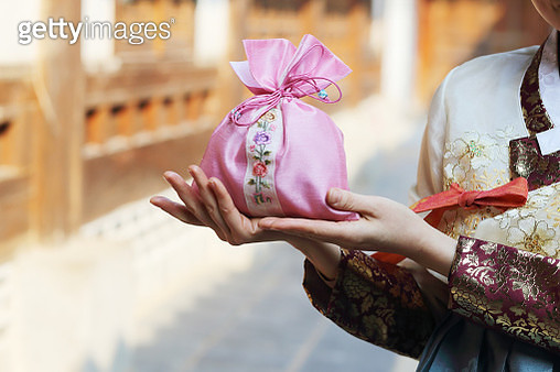 Woman wearing Korean traditional clothes with lucky bag - gettyimageskorea