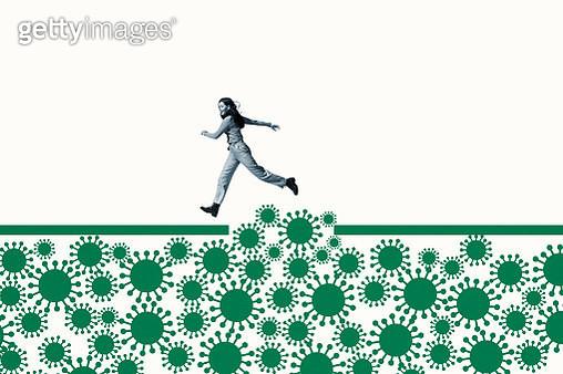Woman jumping over green coronavirus under ramp - gettyimageskorea