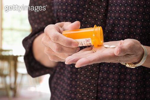 Mixed race woman holding medication pills - gettyimageskorea