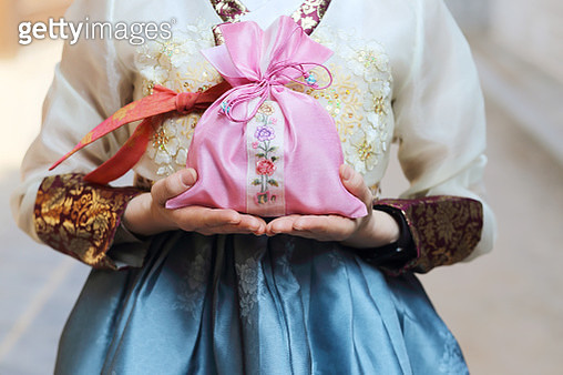 Woman in Korean traditional clothes holding lucky bag - gettyimageskorea