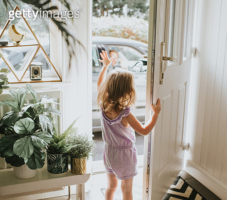 Cute little girl waving out the door in a sunny hallway. - gettyimageskorea