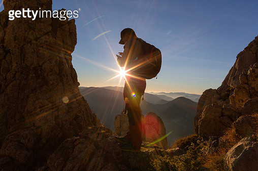 Mid adult man using smart phone in the mountains in sunset - gettyimageskorea