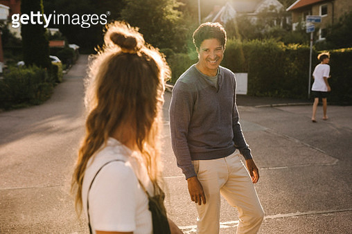 Mature man looking at woman while standing on road during sunny day - gettyimageskorea