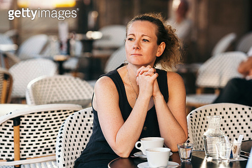 Portrait of a woman sitting at a cafe table in Bordeaux - gettyimageskorea