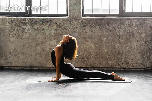 Young woman practicing yoga in urban loft: Upward Facing Dog - gettyimageskorea