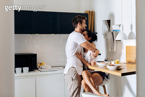 Young couple hugging in kitchen - gettyimageskorea