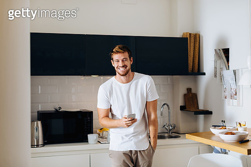 Young man using smartphone in kitchen - gettyimageskorea