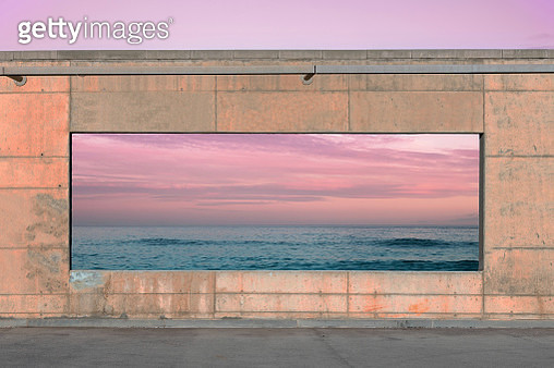 Panoramic window in concrete wall with the view of seascape with sunset sky. - gettyimageskorea