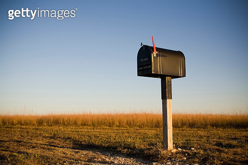 A mailbox stands alone in a Kansas corn field as the sun sets beyond the horizon. - gettyimageskorea