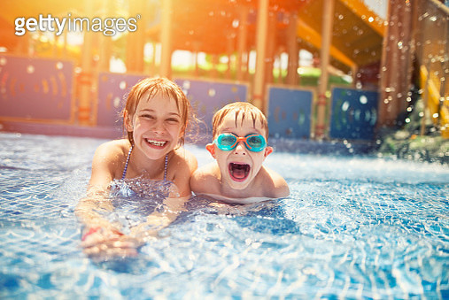 Little girl and her brother lying on front in shallow water in water park. The kids are laughing at camera, the boy is wearing swimming goggles. - gettyimageskorea