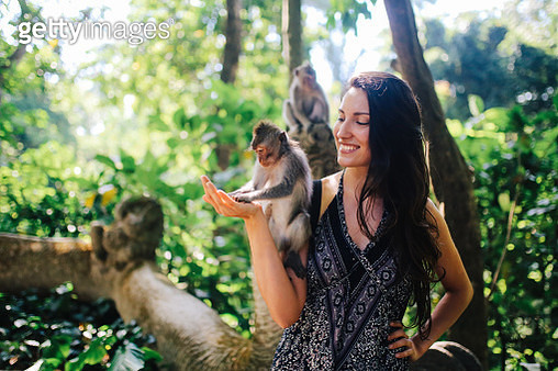 Young woman playing with macaque monkeys near the famous Monkey Forest in Ubud, a small town in Bali, Indonesia. It's a popular natural habitat or a sanctuary with many Hindu temples as well. - gettyimageskorea