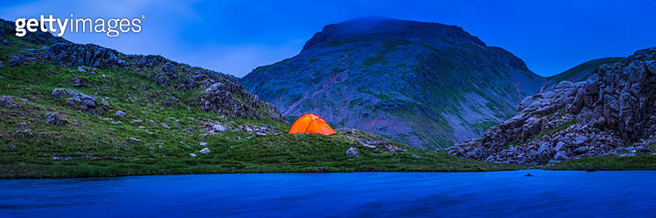 Camping tent glowing in darkening mountain wilderness panorama Lake District - gettyimageskorea
