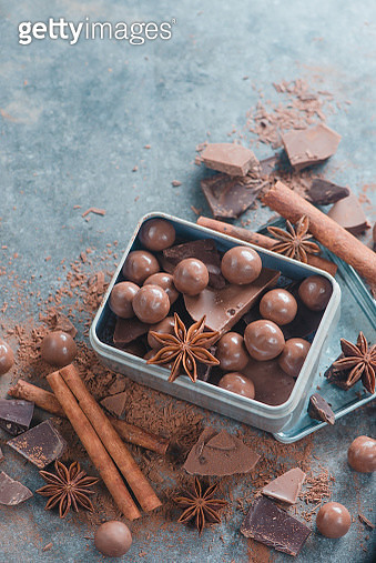 Box with an assortment of chocolates and pieces of broken chocolate with spices, anise stars,... - gettyimageskorea