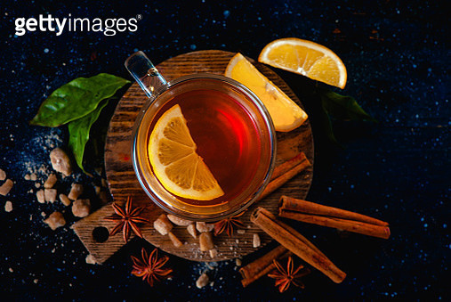 Flat lay still life with glass tea cup, lemon slices, anise stars, sugar, tea leaves and cinnamon... - gettyimageskorea