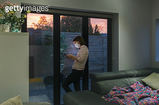 Woman in self isolation using smartphone by window - gettyimageskorea