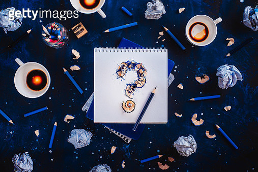 Question mark from pencil shavings with crumpled paper balls, pencils, notepads and empty coffee... - gettyimageskorea