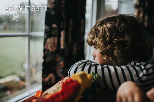 Boy looks out the window on a rainy day. - gettyimageskorea