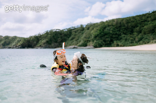 Mother and daughter playing in clear water - gettyimageskorea