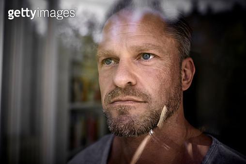 Portrait of mature man looking through window - gettyimageskorea