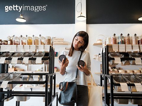 Young woman holding jars in zero waste store - gettyimageskorea