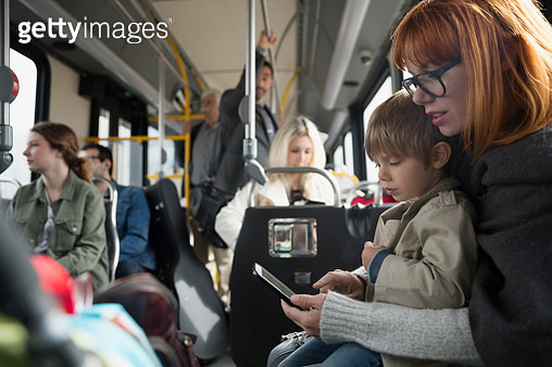 Mother and son using cell phone riding bus - gettyimageskorea