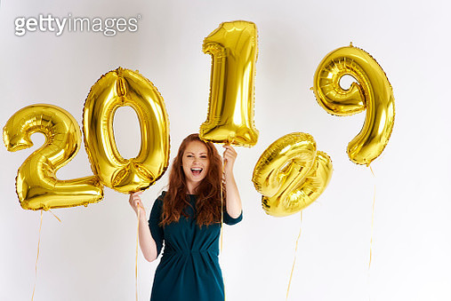 Portrait of happy young woman with golden balloons forming the date '2019' - gettyimageskorea