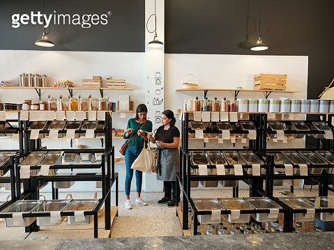 Female costumer and shop assitant looking at products in store - gettyimageskorea