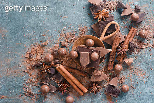 Flat lay with dessert ingredients close-up. Chocolate pieces with spices and scattered cocoa on a... - gettyimageskorea