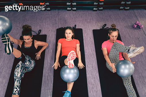 Female Aerobic Team Exercises In Lying Position With Pilates Ball - gettyimageskorea
