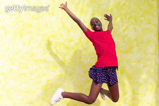 Smiling young woman jumping in air over yellow background. Happy african woman celebrating and dancing outside. Happiness, freedom, motion and people concept. - gettyimageskorea