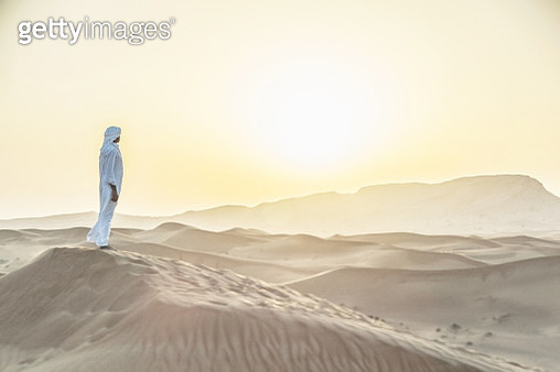 Arab man standing in sand dunes near Dubai. - gettyimageskorea