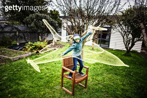 Dream of flying: boy stands on garden chair with arms outstretched and imaginary fighter jet around him. Digital composite. - gettyimageskorea