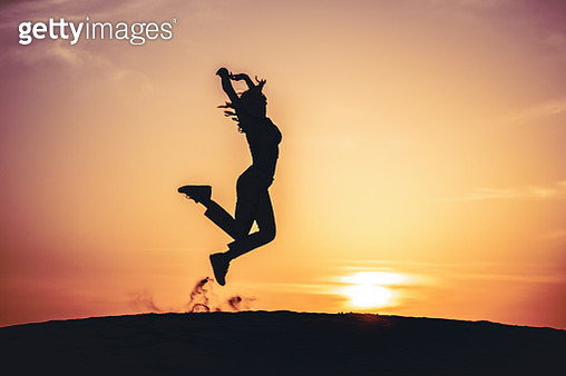 Silhouette Woman Jumping Against Orange Sky During Sunset - gettyimageskorea