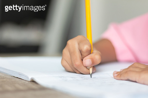 Cropped Hand Of Child Writing On Book With Pencil - gettyimageskorea