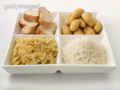 Close up of sectioned plate with bread, potatoes, rice and pasta - gettyimageskorea