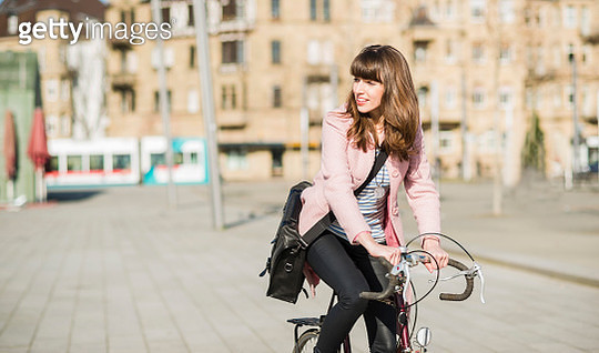 Young woman with bicycle in the city - gettyimageskorea