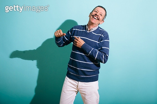 Senior gay man dancing on a Turquoise background laughing and having fun. Part of the LGBTQ Portrait series. - gettyimageskorea
