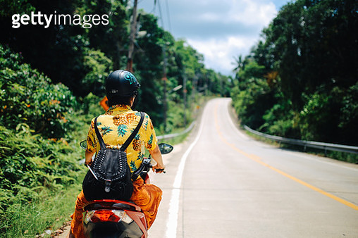 Vintage toned image of a young woman riding a motorcycle through the countryside roads on the island of Ko Phangan, Thailand.   * Note to inspector - the motorcycle front parts are custom / photoshopped to make it look generic/pre-1985. - gettyimageskorea