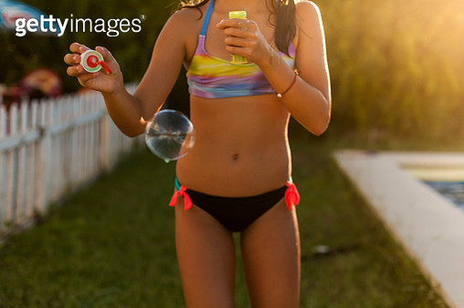 Girl With Bathroom linen blowing bubbles. This in a pool, and it is summer. - gettyimageskorea