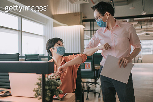 2 asian chinese colleague greeting on each other with new handshake style in office with protective mask on - gettyimageskorea