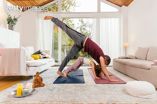 Father and daughter doing yoga together at home - gettyimageskorea