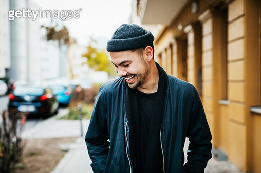 A stylish young man smiling and laughing in a city street, while on the way to meet some friends. - gettyimageskorea
