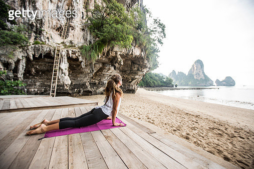 A woman doing a yoga pose on a deck in Thailand. - gettyimageskorea