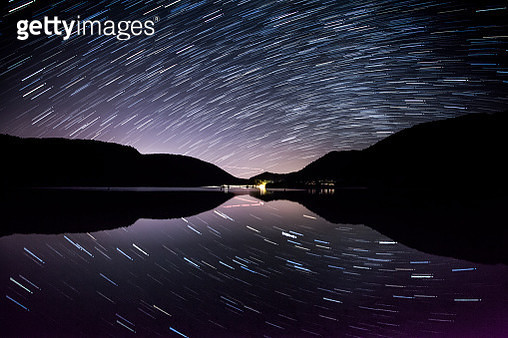 Star trails over calm lake, New Zealand - gettyimageskorea