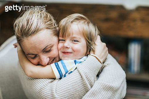 Affectionate mother and son embracing at home. - gettyimageskorea
