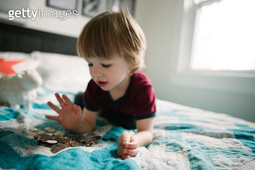 Boy counting coins on bed - gettyimageskorea